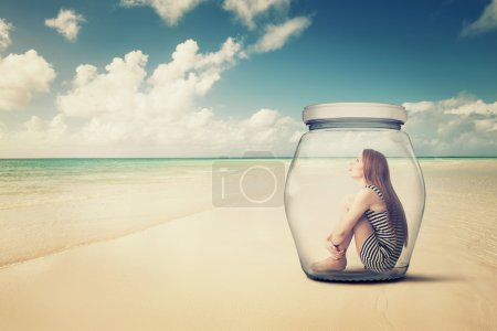 woman sitting in a glass jar on a beach looking at the ocean view