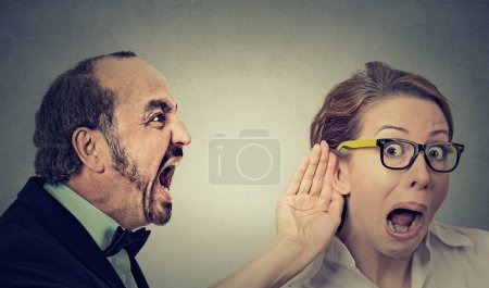 angry man screaming curious woman with hand to ear gesture listens