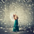 Excited young woman with umbrella under a money ra...