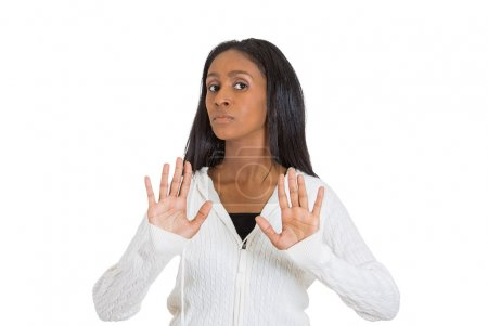 Displeased woman raising hands up to say no stop right there