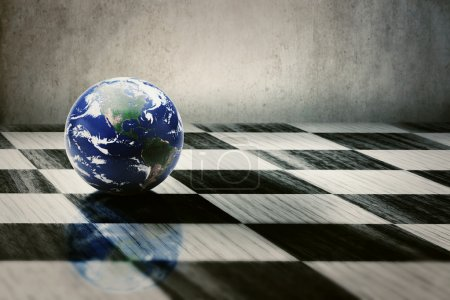 Photo pour World earth on a chessboard isolated on grey wall background. Elements of this image furnished by NASA - image libre de droit
