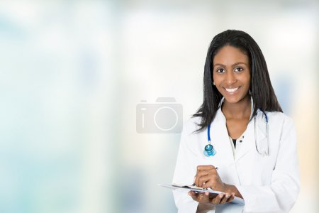 confident happy female doctor medical professional writing notes