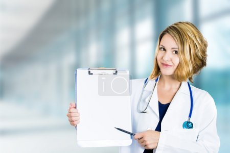 Happy smiling doctor with clipboard standing in hospital hallway