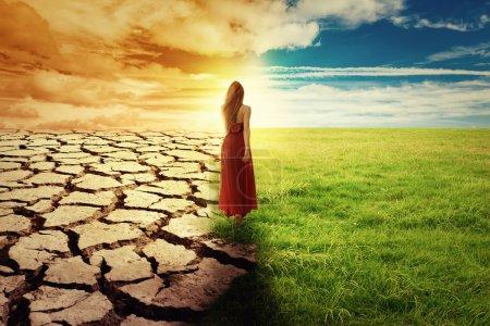 Photo pour Une image conceptuelle du changement climatique. Paysage d'herbe verte et de terres arides. Femme en robe verte marchant à travers un champ ouvert - image libre de droit