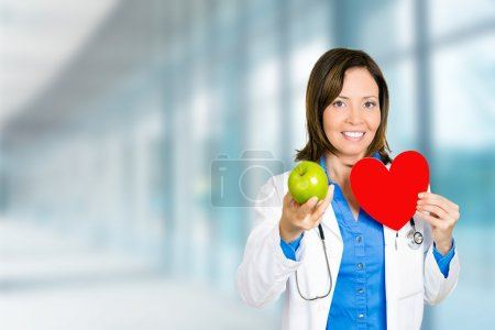 female doctor healthcare professional with red heart green apple