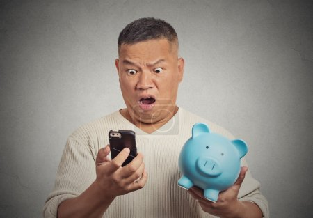 Photo for Portrait shocked man looking at his smart phone holding piggy bank - Royalty Free Image