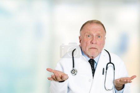 Photo pour Portrait de plan rapproché désemparé le médecin professionnel de soins de santé aîné sans-point avec le stéthoscope, n'a aucune réponse, ne sait pas le diagnostic droit restant dans le fond isolé de fenêtre de bureau de clinique de couloir d'hôpital - image libre de droit