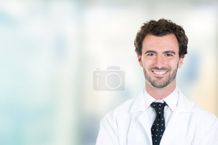 young male doctor smiling standing in hospital hallway