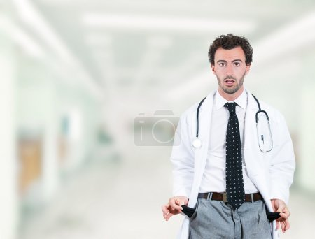 doctor penniless showing empty pockets standing in hospital hallway