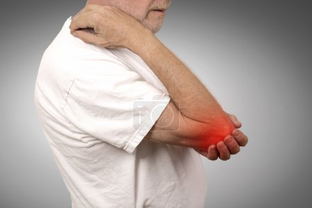 senior man with elbow inflammation colored in red suffering from pain