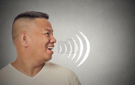 Foto de Retrato de perfil lateral joven hablando con ondas sonoras saliendo de su boca abierta de fondo de pared gris aislado. Expresiones de rostro humano - Imagen libre de derechos