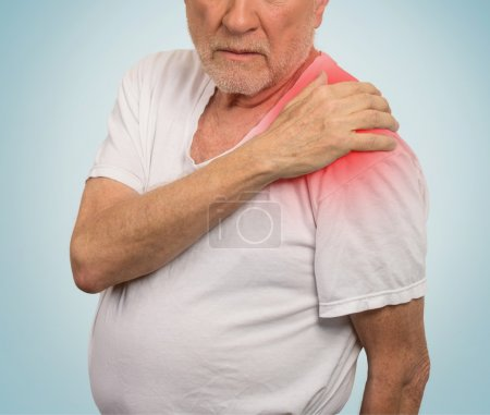 senior man with pain in his shoulder isolated blue background