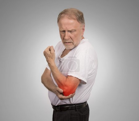 Photo for Closeup senior man with elbow inflammation colored in red suffering from pain and rheumatism isolated on gray wall background with copy space - Royalty Free Image