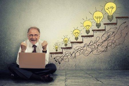 Photo pour Heureux heureux homme exécutif senior travaillant sur ordinateur, assis sur un sol en parquet célèbre la réussite en affaires, promotion, croissance de l'entreprise isolé sur fond de texture de mur gris - image libre de droit
