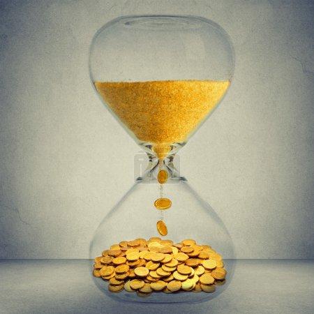 Photo pour Le temps est argent concept de possibilité financière. Horloge de sable avec poussière d'or et pièces isolées sur fond de mur gris - image libre de droit