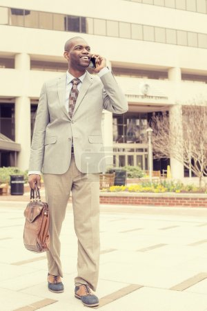 Happy business man talking on his phone while walking outside