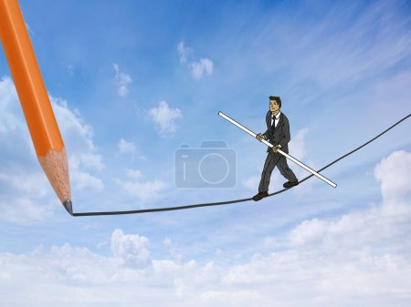 Young businessman balancing on tight rope
