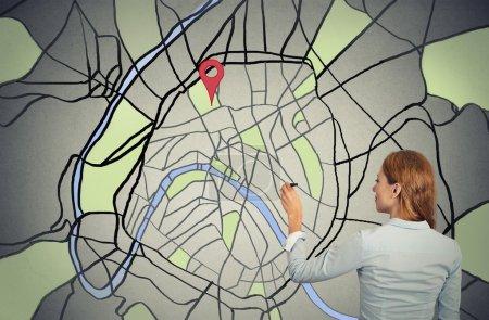 junge Geschäftsfrau zeichnet auf einer Landkarte
