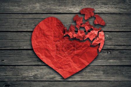Photo pour Cœur brisé concept de séparation et icône de divorce. Papier rouge froissé en forme d'amour déchiré sur le vieux bois symbole de problèmes médicaux cardiovasculaires de soins de santé dus à la maladie - image libre de droit