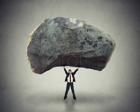 Photo for Power of leadership with the ability to inspire as a businessman lifting up a huge boulder removing a large obstacle and leading by example as a business concept of success and determination - Royalty Free Image
