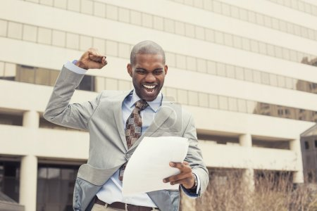 Successful man celebrates success holding new contract documents