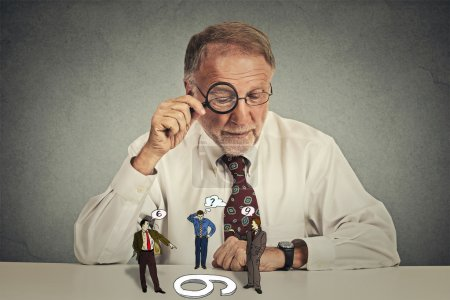 man skeptically looking at arguing people through magnifying glass