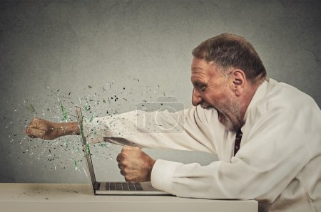 Photo for Furious senior businessman throws punch into computer screaming isolated grey office wall background. Negative human emotions, facial expressions, feelings, aggression, anger management issues concept - Royalty Free Image