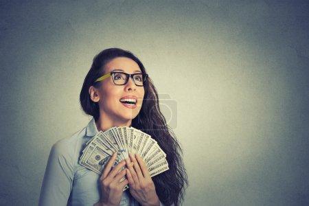 Photo pour Verticale de plan rapproché heureuse a excité la jeune femme d'affaires réussie retenant des billets d'argent d'dollar dans le fond gris isolé de mur d'isolement de main. Sensation positive d'expression faciale d'émotion. Récompense financière - image libre de droit
