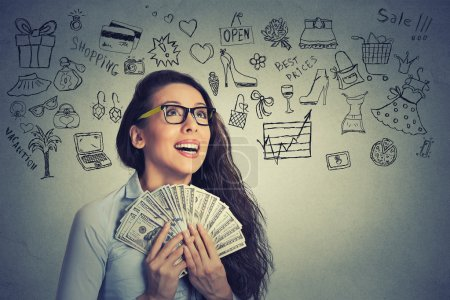 excited successful young business woman holding money