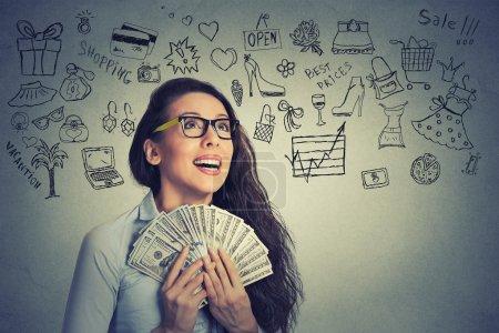 Photo pour Verticale de plan rapproché heureuse a excité la jeune femme d'affaires réussie retenant des billets d'argent d'dollar dans le fond gris isolé de mur d'isolement de main avec des graphiques d'info. Expression faciale positive d'émotion. Récompense financière - image libre de droit