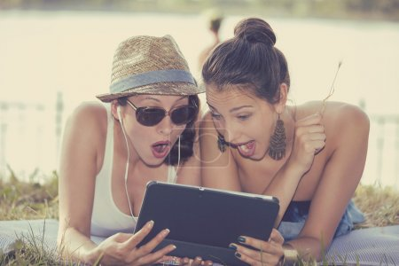 two surprised girls looking at pad discussing latest gossip news