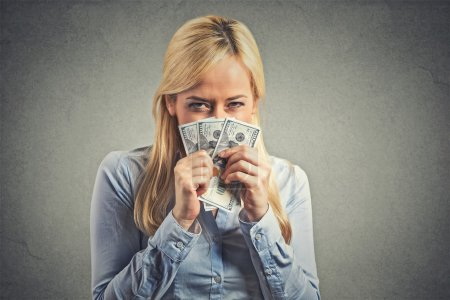 Greedy young woman, holding tight dollar banknotes
