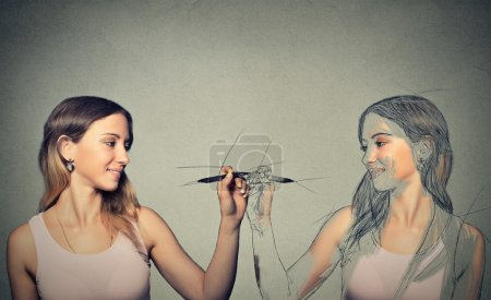 Photo for Create yourself, your future destiny, image, career concept. Attractive young woman drawing a picture, sketch of herself on grey wall background. Human face expressions, determination, creativity - Royalty Free Image