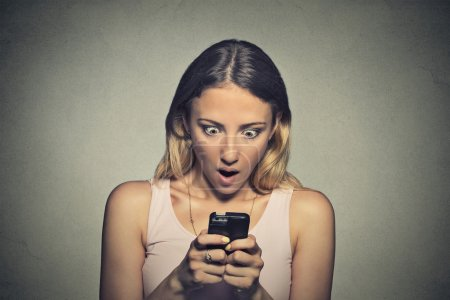 anxious young girl looking at phone seeing bad news