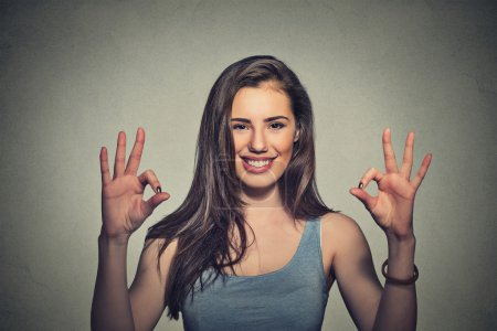 Photo for Excited happy young optimistic woman giving ok sign gesture with two hands isolated on gray wall background. Positive human emotions face expression body language - Royalty Free Image