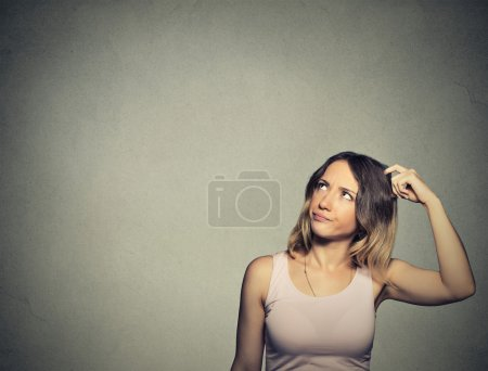 woman scratching head, thinking daydreaming about something looking up