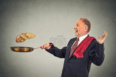Photo for Happy smiling senior man tossing pancakes on frying pan isolated on gray wall background. Positive face expression emotion, Kitchen fun concept - Royalty Free Image
