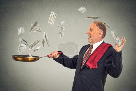 Photo pour Happy senior elderly business man juggling money dollar bills banknotes isolated on grey wall background - image libre de droit