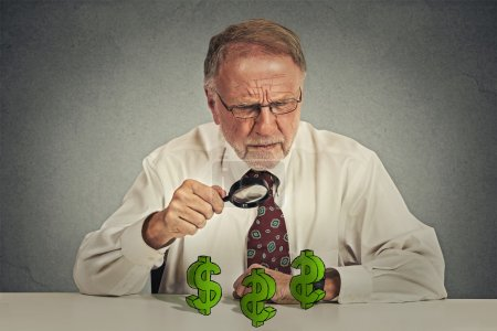 skeptical business man looking through magnifying glass at dollar sign symbol
