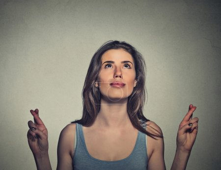 young woman crossing her fingers looking up