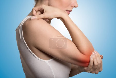woman with painful elbow on blue background