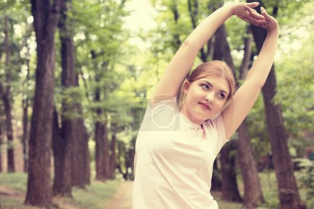 Fitness woman stretching exercises on fresh air