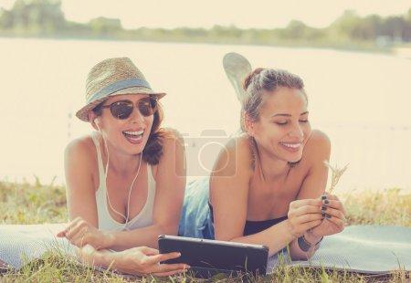 Photo pour Deux jeunes femmes heureuses drôles amis riant parcourant regarder des blogs de vidéos de médias sociaux écoutent la musique sur l'ordinateur intelligent de garniture se étendant à l'extérieur sur le pré vert le jour ensoleillé d'été - image libre de droit