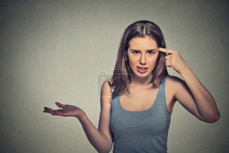 Photo for Closeup portrait of angry mad young woman gesturing with her finger against temple asking are you crazy? Isolated on gray wall background. Negative emotions facial expression feeling body languag - Royalty Free Image