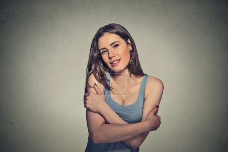 confident smiling woman holding hugging herself