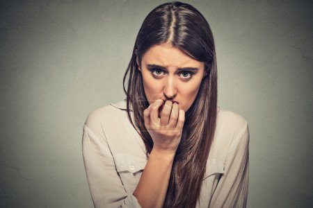 Photo for Closeup portrait young unsure hesitant nervous woman biting her fingernails craving for something or anxious, isolated on gray wall background. Negative human emotions facial expression feeling - Royalty Free Image