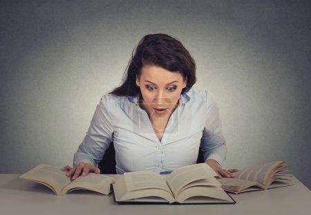 Photo pour Portrait jeune choqué femme assise au comptoir avec beaucoup de livres ouverts de lecture isolé mur gris fond. grimace expression émotion sentiments problème perception réaction - image libre de droit