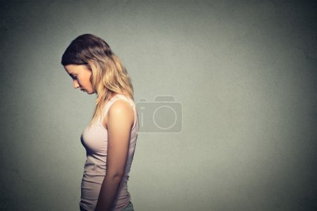 Photo for Sad lonely young woman looking down isolated on gray wall background - Royalty Free Image