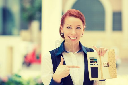 smiling business woman holding pointing at many credit cards in her wallet