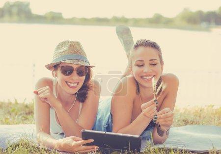 Photo pour Deux drôles de jeunes amies heureuses qui rient en parcourant le partage en regardant des vidéos de médias sociaux blogs sur un ordinateur portable en plein air sur une prairie verte le jour ensoleillé de l'été - image libre de droit